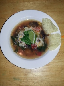 Tortilla soup with cilantro, shredded cheese, wedge of lime, and tortilla chips